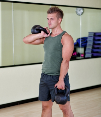 Young man working out with kettlebells in gym, standing photo