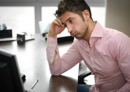 Tired or frustrated young man working in office looking at computer screen