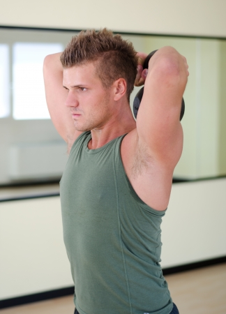 Young man working out with kettlebell in gym, standing photo