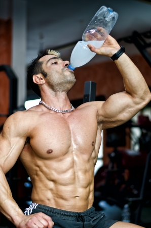 Muscular male bodybuilder in a gym drinking water or energy drink from bottle Stock Photo
