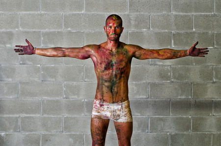 Handsome young man with skin all painted with colors, arms spread open photo