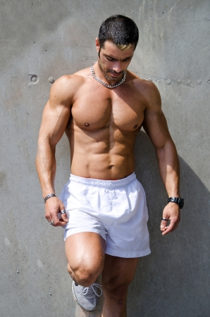 Muscular male bodybuilder standing against wall outdoors shirtless, wearing white boxer shorts photo