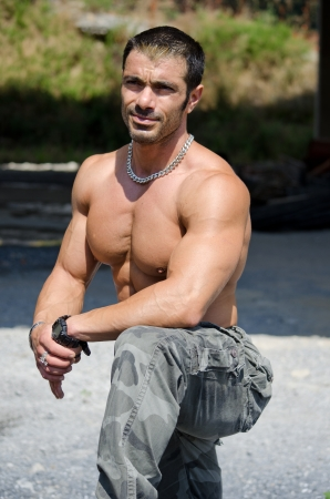 Muscle man shirtless outdoors in building site resting after construction work photo