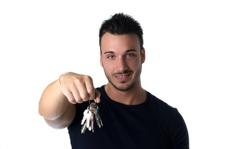 Handsome young man holding bunch of keys, looking in camera, isolated on white photo