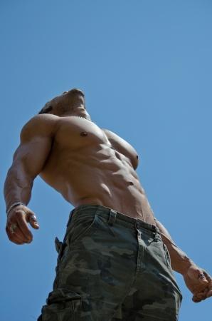 Muscular joven sin camisa culturista masculino mirando hacia arriba en el cielo, visto desde abajo Foto de archivo - 22627040