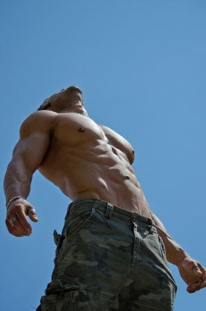 Muscular young male bodybuilder shirtless looking up in the sky, seen from below Фото со стока