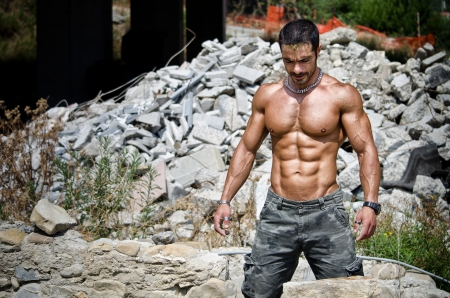 Muscle man shirtless outdoors in building site  Construction worker