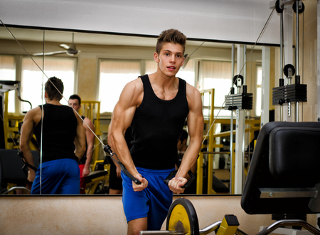 pecs: Teen bodybuilder working out with gym equipment, exercising pecs muscles with cables Stock Photo
