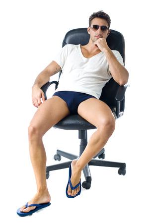 desnudo masculino: Hombre joven atractivo en camiseta, con las piernas desnudas en la silla de oficina, aisladas sobre fondo blanco