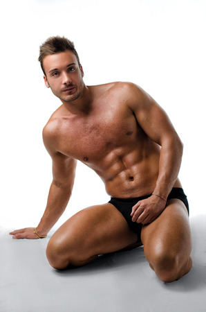 Handsome, fit, young man on his knees showing muscular naked body photo