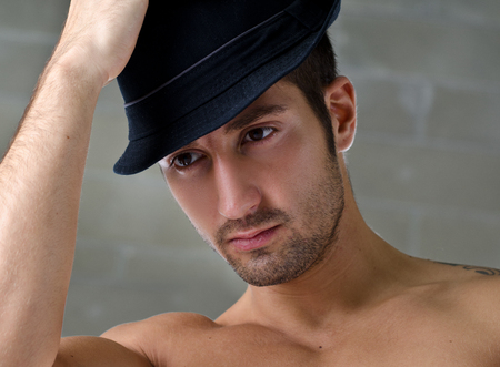 Head-shot of attractive shirtless young man wearing hat, looking off camera photo