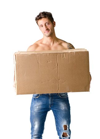 Attractive shirtless young man holding and carrying big cardboard box, isolated on white