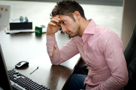 preoccupied: Preoccupied, worried young male worker staring at computer screen in his office