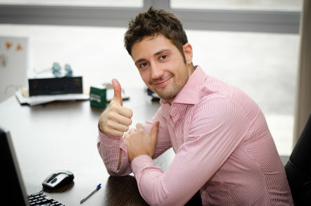 Cheerful office worker at desk doing thumb up sign and smiling. Real workplace photo