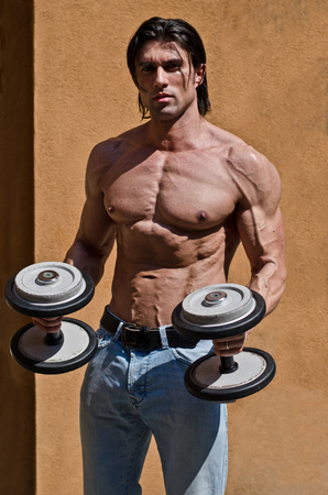 Muscular young bodybuilder shirtless outdoors in jeans, exercising biceps with dumbbells photo
