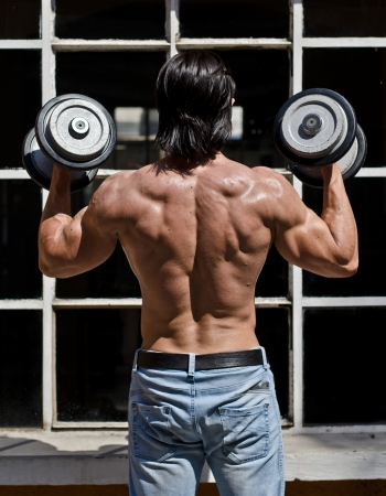 Back of muscular young bodybuilder shirtless outdoors in jeans, exercising biceps with dumbbells photo