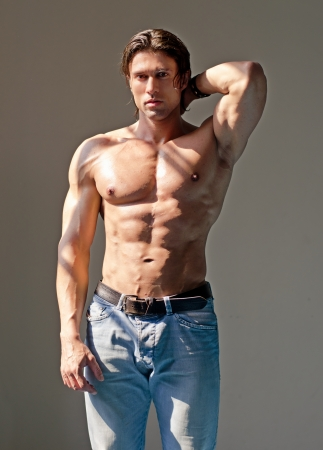 Handsome muscular man shirtless wearing jeans with hand behind his head photo