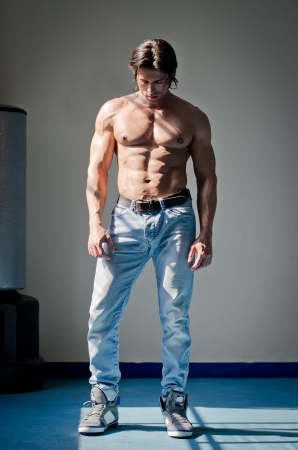 Full figure shot of muscular man shirtless in jeans, looking down photo