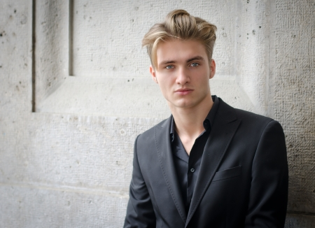 Attractive blond young man in shirt and jacket, standing against wall photo