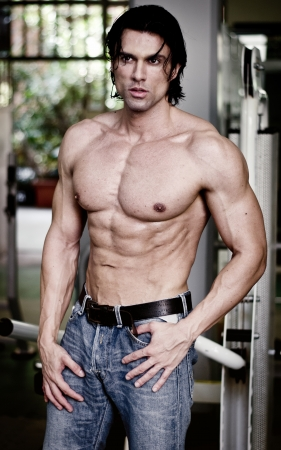 Handsome muscular man in jeans shirtless looking away, showing ripped torso