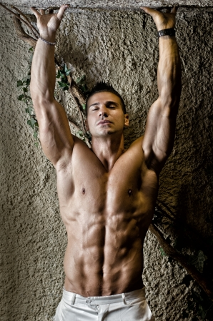 Handsome muscular man shirtless wearing white pants, arms up, in front of concrete wall photo