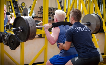 squat: Personal trainer helping young male client in gym during workout on equipment Stock Photo