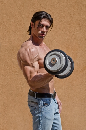 Muscular young bodybuilder shirtless outdoors in jeans, exercising bicep with dumbbell photo