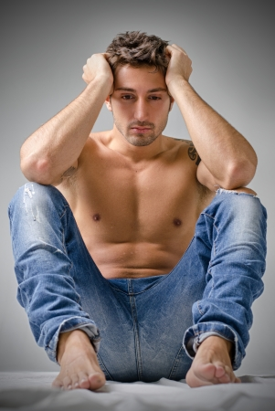 Depressed or sad handsome young man shirtless in jeans, sitting on floor with head in his hands photo