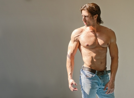 Handsome muscular man shirtless wearing jeans on grey background