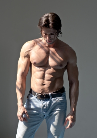 Handsome muscular man shirtless wearing jeans on grey background looking down photo