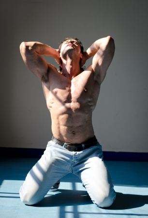 Attractive muscleman kneeling shirtless on grey background with hands behind head, looking up