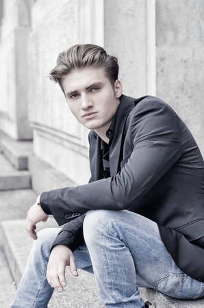 looking good: Attractive blond young man in jeans and jacket, sitting outdoors looking in camera