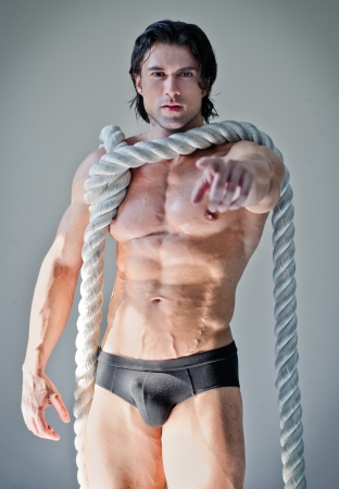 Muscular man in underwear with heavy, big rope around neck, pointing finger at camera photo