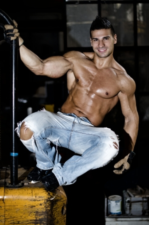 Handsome, muscular young man smiling, shirtless in jeans