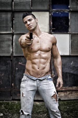 Menacing, muscular young man shirtless pointing handgun to camera outdoors photo