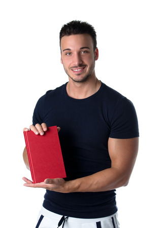 Smiling young man holding and showing book cover and looking in camera photo
