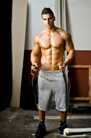 Athletic, muscular young boxer shirtless with jumping rope ready to jump photo