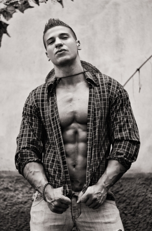 Handsome, muscular young man with open shirt, jeans and straw hat outdoors, black and white shot photo