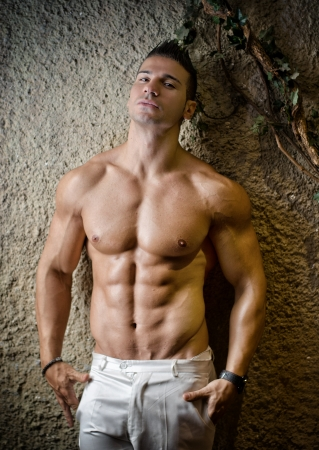 Handsome muscular man shirtless wearing white pants, in front of concrete wall