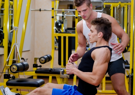 Personal trainer helping young male client in gym during workout on equipment photo