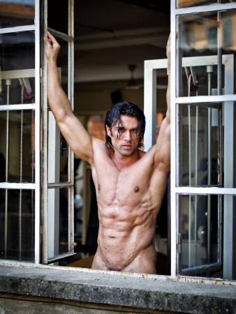 Handsome muscular man naked looking in camera on window frame, showing ripped torso
