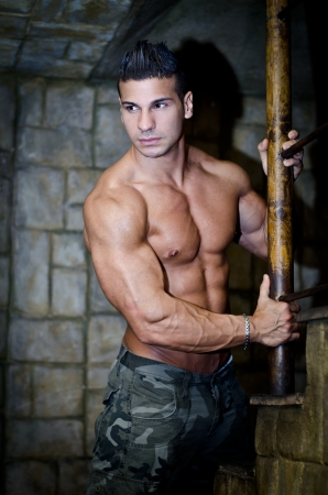Handsome muscular man shirtless wearing military pants, in front of stone wall photo