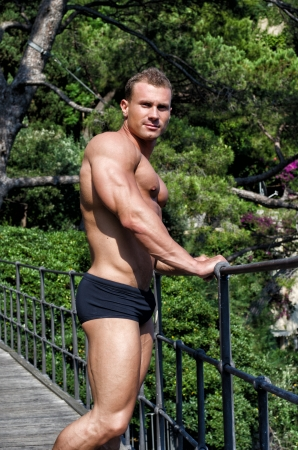 Muscular shirtless young bodybuilder outdoors looking in camera, wearing only swimming suit photo