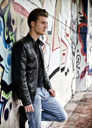 Attractive blond haired young man standing against graffiti wall photo