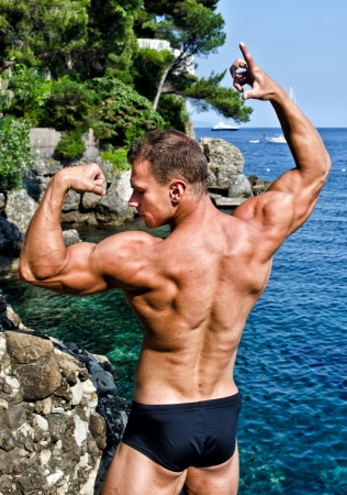 Muscular young bodybuilder outdoors  photo