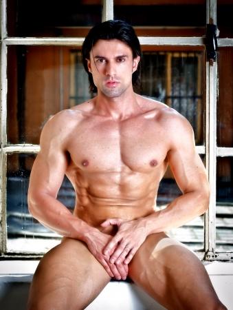 nudo maschile: Muscoloso giovane bodybuilder completamente nudo seduto, nascondendo cavallo mentre seduta sulla finestra