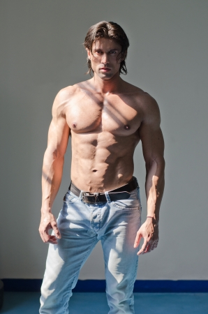 Handsome muscular man shirtless wearing jeans on grey background looking in camera photo