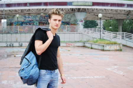 ruck sack: Handsome blond, blue eyed young man outdoors with ruck sack on shoulder, t-shirt and jeans