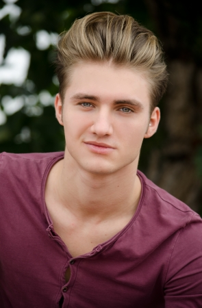 Attractive blue eyed, blond young mans head shot outdoors, looking at camera Stock Photo