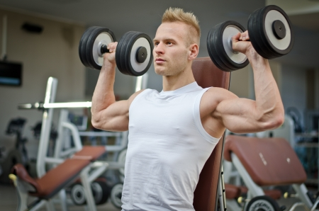 Attractive young man training shoulders with dumbbells sitting on bench in gym